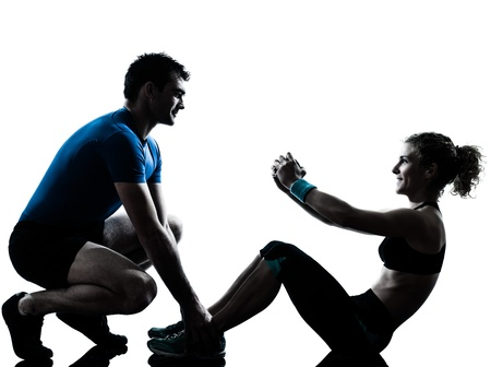 fitness trainer: one caucasian couple man woman personal trainer coach exercising abdominal silhouette studio isolated on white background