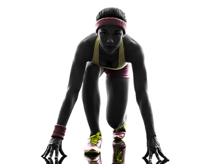 one caucasian woman runner running  on starting blocks  in silhouette on white background photo