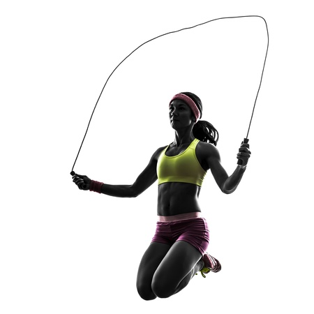 one caucasian woman exercising fitness  jumping rope  in silhouette on white background photo