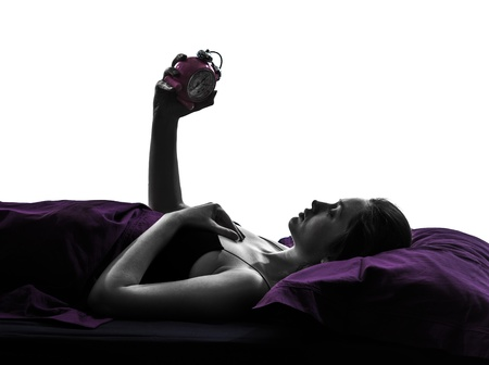 shadow woman: one woman in bed looking at alarm clock silhouette studio on white background Stock Photo