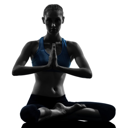 shadow: one caucasian woman exercising yoga meditating in silhouette studio isolated on white background Stock Photo