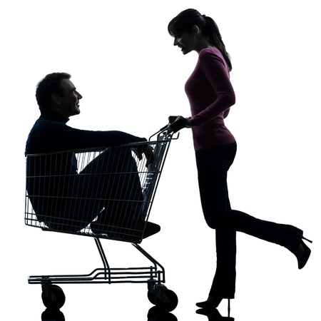 one caucasian couple woman  with man sitting in shopping cart   in silhouette studio isolated on white background