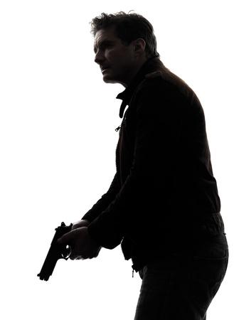 한 남자 킬러 경찰관 총을 들고 스튜디오 실루엣 흰색 배경