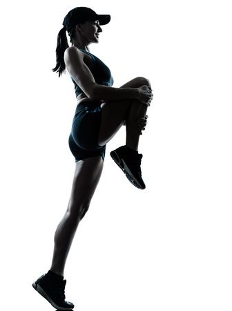 leg calf injury: one caucasian woman runner jogger stretching legs in silhouette studio isolated on white background