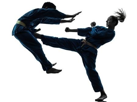 artes marciales: una pareja hombre mujer el ejercicio de karate artes marciales vietvodao en el estudio de la silueta aislado en el fondo blanco