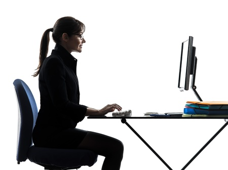 profile view: one business woman computer computing typing  silhouette studio isolated on white background