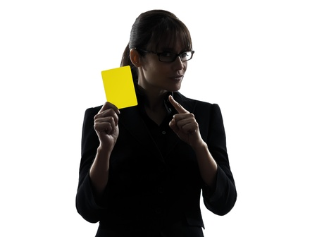 one business woman showing yellow card  silhouette studio isolated on white background