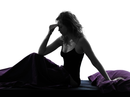 one woman headache hagover sitting on bed silhouette studio on white background photo