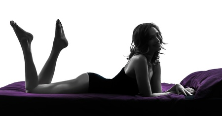 one beautiful young woman in bed full length in bed silhouette studio on white background