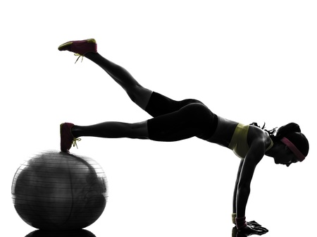 plank position: one  woman exercising fitness workout plank position on fitness ball in silhouette  on white background