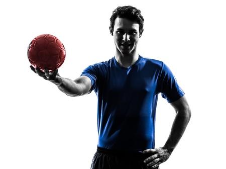 balonmano: un joven cauc?co ejercicio jugador de balonmano en el estudio de la silueta sobre fondo blanco Foto de archivo