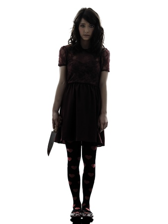 female assassin: one caucasian strange young woman killer holding  bloody knife in silhouette white background Stock Photo