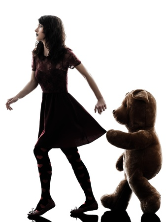 vicious: one caucasian strange young woman and vicious teddy bear  in silhouette white background