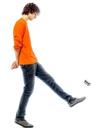 profile view: one young man caucasian kicking tin can sad bore side view   in studio white background Stock Photo