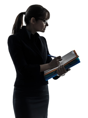 taking notes: one business woman holding folders files writing  silhouette studio isolated on white background