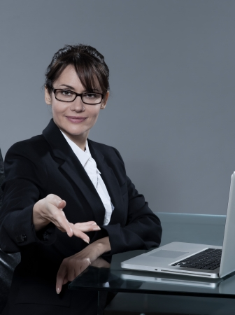 beautiful cheerful caucasian  business woman sitting at desk on isolated background photo