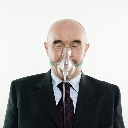 suffocating: senior man portrait studio wearing oxygen mask