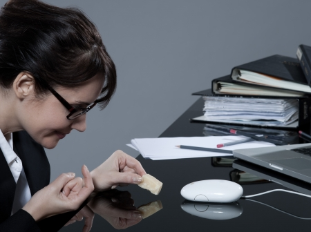 indolence: beautiful brunette business woman at her desk trying to trap her computer mouse with cheese