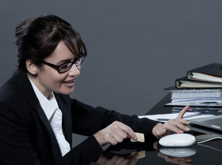beautiful brunette business woman at her desk trying to trap her computer mouse with cheese