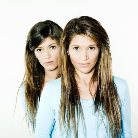 arrogancia: foto de estudio retrato sobre fondo aislado de dos hermanas gemelas amigas