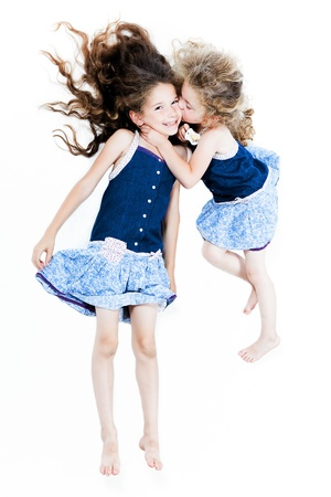 two caucasian little girls kissing afection isolated studio on white background photo