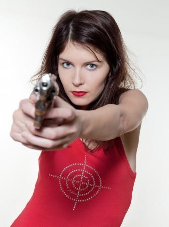 mujer con pistola: estudio de retrato de una bella mujer en aislados sobre fondo blanco que apunta el arma Foto de archivo