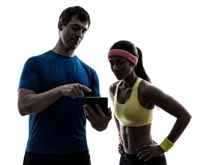 kavkazský: jedna žena cvičení fitness cvičení s člověkem trenérem pomocí digitálního tabletu silueta na bílém pozadí