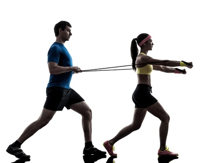 one  woman exercising resistance  rubber band fitness workout with man coach in silhouette  on white background Stock Photo - 21283608