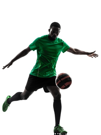 indoor soccer: one african man soccer player green jersey kicking in silhouette  on white background