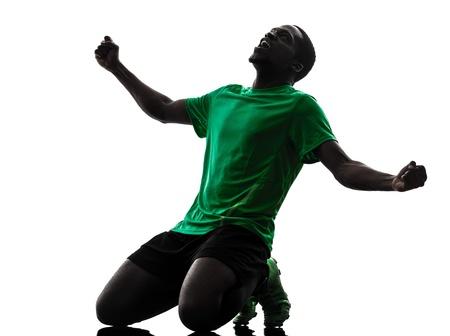 arrodillarse: un jugador de f�tbol hombre africano celebrando la victoria maillot verde de la silueta en el fondo blanco Foto de archivo