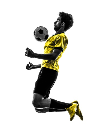 cut the competition: one brazilian soccer football player young man in silhouette studio  on white background Stock Photo