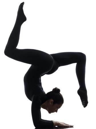 한 백인 여자는 흰색 배경에 실루엣 체조 요가 연습 contorsionist