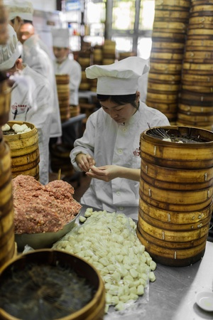 fang: Shanghai, China - April 7, 2013: people preparing dim sum Shanghai style steamed pork dumplings at the Nanxiang Steamed bun shop in Fang Bang Zhong Lu old city  at the city of Shanghai in China on april 7th, 2013