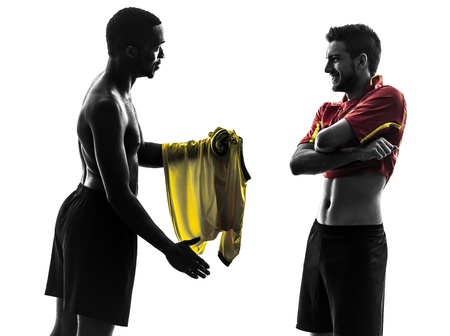 cut the competition: two men soccer player playing football competition exchanging jersey  in silhouette  on white background