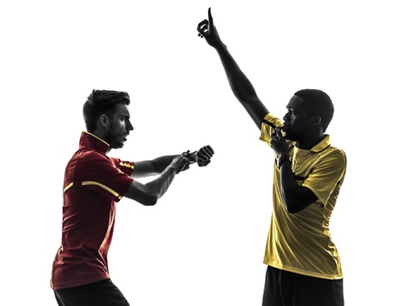 two men soccer player and referee blowing whistle in silhouette  on white background photo