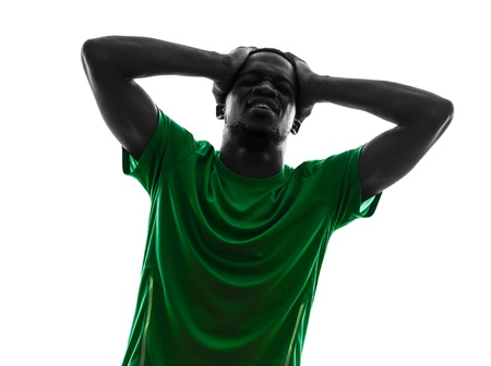 one african man soccer player green jersey despair loosing in silhouette  on white background photo