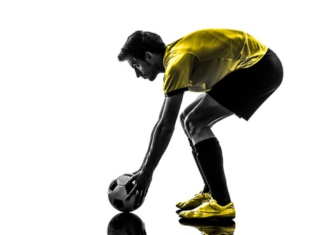 one brazilian soccer football player young man preparing free kick in silhouette studio  on white background Stock Photo - 21493103