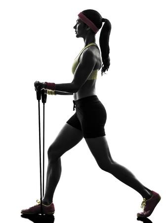 una mujer en el ejercicio de fitness bandas de resistencia del entrenamiento en la silueta en el fondo blanco photo