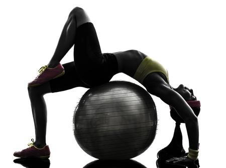 een soepele vrouw uitoefening fitness workout op fitness bal in silhouet op een witte achtergrond Stockfoto