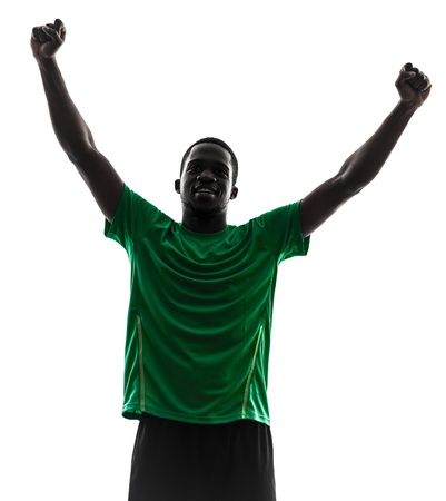 black shadow: one african man soccer player celebrating victory green jersey in silhouette  on white background Stock Photo