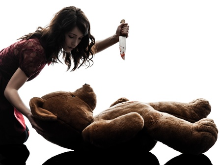 one caucasian strange young woman killing her teddy bear  in silhouette white background photo