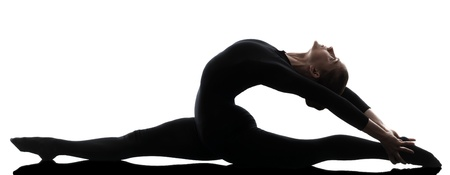 gymnastics: one caucasian woman contortionist practicing gymnastic yoga  in silhouette   on white background