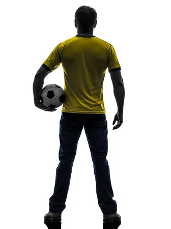 one caucasian man holding soccer football silhouette rear view back  in silhouette on white background photo