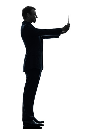 one caucasian business man holding photographing digital tablet   in silhouette on white background photo