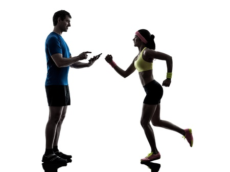 one  woman exercising jogging with man coach using digital tablet  in silhouette  on white background photo