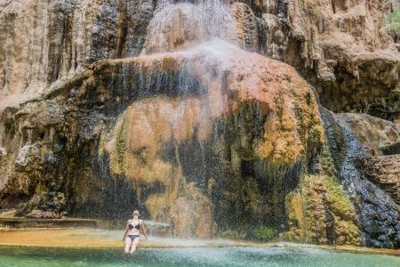 hot springs: one woman bathing at main hot springs waterfall  in jordan middle east
