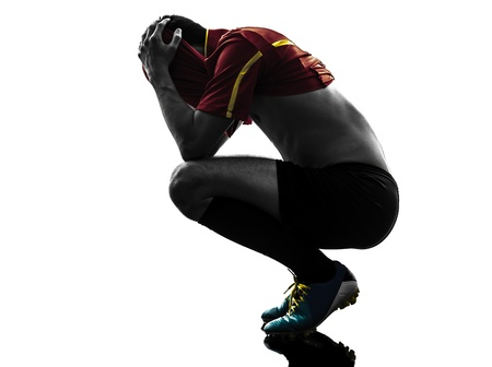 vanquish: one man soccer player  loosing despair playing football competition in silhouette  on white background Stock Photo