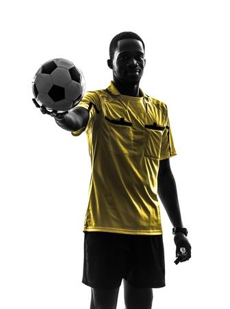 arbitros: un hombre africano árbitro celebración de pie mostrando fútbol en silueta sobre fondo blanco