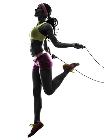 een blanke vrouw uitoefening fitness springtouw in silhouet op een witte achtergrond