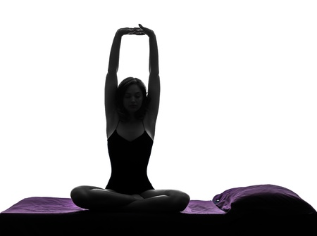 one woman waking up stretching arms in bed silhouette studio on white background photo
